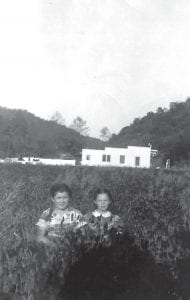 The daughters of John B. Adams, Donna Adams Rowe (left) and Danna Adams Richardson, were photographed in a field beside the John B. Adams Store in Isom in the 1950s.