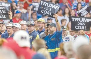 A group of coal miners held signs as President Donald Trump took the stage at a rally in support of the Senate candidacy of West Virginia's Attorney General Patrick Morrisey Tuesday at the Charleston Civic Center in Charleston, W.Va. (Craig Hudson/Charleston Gazette-Mail via AP)