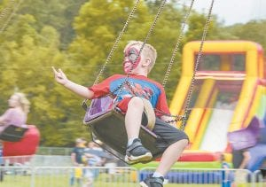 MORE FESTIVAL FUN — Disguised as Spiderman, Colton Smith was slinging a web while spinning on the swings at the Isom Days Carnival. Next up during Letcher County's fall festival season is Neon Area Days, which begins Friday (September 7) on Main Street in Neon. (Photo by Chris Anderson)