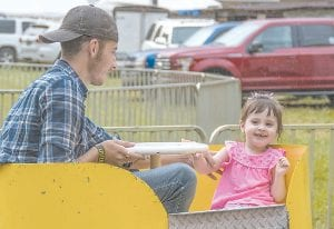 Karlie Logic smiles while taking a ride with Doug Niece at the Isom Days carnival Friday night.