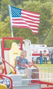 Brady Baker and the Stars and Stripes fly around on the Whirly Bird at the Isom Days carnival.