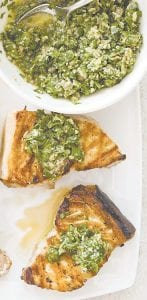 """This photo shows grilled swordfi sh steaks with salsa verde. This recipe appears in the cookbook """"Master of the Grill."""" (Daniel J. van Ackere/America's Test Kitchen via AP)"""