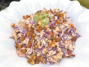 This photo shows Confetti Coleslaw from a recipe by Elizabeth Karmel. It is vibrant and pleasing to the eye, chock full of veggies, and the dressing is spiced with cumin, paprika and cilantro which are perfect companions to ribs with a spice-rub that includes some of the same flavors. (Elizabeth Karmel via AP)