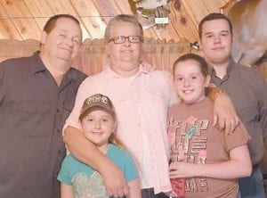 Rick Collins stands with his wife, Ivealue, and three grandchildren, the Reverend Jon-Dawson Fields, Lacie Isabella Fields, and Maggie Jane Fields.