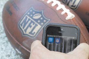 Apps for NFL and Yahoo Sports are displayed on a phone on the sidelines. For the new regular season, the league is finally dropping a requirement that viewers sign in with a cable or satellite subscription as it seeks to expand its online audience at a time when TV ratings are declining. The subscription-free games will be available on the NFL app and the Verizon-owned Yahoo Sports, Tumblr and AOL apps. (AP Photo)