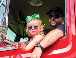 2-year-old Alivia Wright waves while riding in a fire truck with her dad, Neon firefighter Taylor Wright.