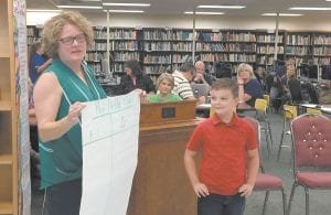 Teacher Lynn Gilliam with third-grader Damon Church and his Plus Delta Chart at the Jenkins board meeting.