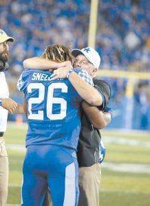 Benny Snell hugged coach Mark Stoops after UK beat then No. 14 Mississippi State 28-7. (Vicky Graff Photo)