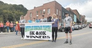 Mountain Heritage Festival 5K and 10K winners Abby Bentley, Jacob Smith, Keith Adams, Dan Brennan, Brandy Cook and Javier Polly marched in Saturday's parade.