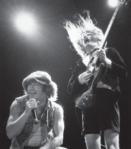 "When AC/DC marked their first Top 40 hit! This week in 1985, AC/DC vocalist Brian Johnson (left), lead guitarist Angus Young and bandmates Malcolm Young, Phil Rudd and Cliff Williams were celebrating their first pop Top 40 hit, ""You Shook Me All Night Long,"" which entered the charts on October 25, 1980. According to The History Channel, AC/DC rank as the 10th-highest-selling recording artists of all time with 71 million albums sold — 30 million fewer than Led Zeppelin, but roughly five million more than both the Rolling Stones and Aerosmith and nearly 15 million more than both Metallica and Van Halen. (AP Photo/Houston Chronicle, Timothy Bullard)"