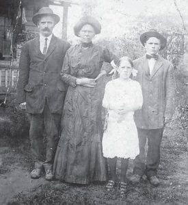 Pictured is Flora Flanary, at age six or seven, with her Aunt Malvina, Malvina's husband Francisco, and an orphan boy named Edd whom they took in.