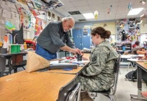 Doug Adams celebrated his 85th birthday on November 3, and student Allison Caudill work on a project in Adams's Letcher Central High School classroom. He is employed at the high school as a full-time teacher. (Photo by Jennifer Honeycutt)