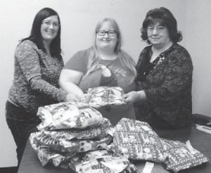 Shirley Sexton and Grayson Holbrook recently delivered gift packages containing pajamas for each Letcher County child who is now in foster care. The women presented the gifts to Heather Caudill, who will distribute them to the children.