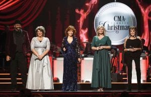 "Host Reba McEntire, center, with members of The Isaacs, from left, Ben Isaacs, Becky Isaacs Bowman, Sonya Isaacs Yeary and Lily Isaacs during the ninth annual ""CMA Country Christmas"" airing Monday, Dec. 10, at 8 p.m. on ABC. (ABC via AP)"