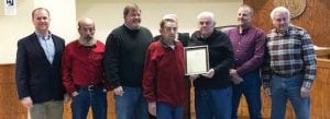 BUDDY GRUBB (fourth from left) was presented with a plaque at Monday's December meeting of the Letcher County Fiscal Court in honor of Grubb's work with the Letcher County Veterans Museum in downtown Whitesburg. Holding the plaque with Grubb is District Five Magistrate Wayne Fleming. District Two Magistrate Terry Adams and District One Magistrate Bobby Howard stand next to Fleming on the photo's right side. Others pictured (from far left) are County Attorney Jamie Hatton, District Three Magistrate Woody Holbrook, and County Judge/ Executive Jim Ward. District Four Magistrate Keith Adams is standing behind Grubb and cannot be seen.