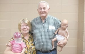 Bessie and Lester McPeek, co-founders and directors of God's Love from a Diaper Bag in Jenkins hold the infant simulators they use to teach about prenatal and infant care. (WMU photo by Pam Henderson)