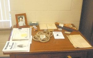 Letcher Circuit Clerk Mike Watts has laid items stored in the clerk's office for more than 100 years on a table in his office for viewing. A picture of Floyd Frazier, records of his trial, and the rope used to hang him are among the items, along with a billy club used as evidence in a police brutality trial and a sample ballot from the 1956 General Election. The hangman's noose that had been tied in the rope is missing.