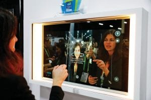 A woman demonstrates the Artemis smart mirror at CES International in Las Vegas. The interactive mirror has video capture, virtual try-ons, facial and object recognition, and can give the user video instruction on specific makeup products, among other things. (AP Photo)