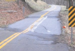 SINKING FEELING — Rounding a curve on KY 1103 near Ingrams Creek, a section of road looks to be relatively level, but actually drops off nearly a foot. Highway department officials say they have asked for money to fix some of the roads in the county, but the loss of coal severance tax has left the budget very tight. (Photo by Sam Adams)