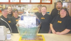 A FRIEND IN NEED — Employees of Lee's Fried Chicken in Whitesburg came to the aid of co-worker Jonathan Day after his foot had to be amputated due to complications of diabetes. Day, now 41, has been off work for nearly two years and did not have insurance. The employees are raffling off a basket to help him and his wife, Alicia Anderson, keep their house and car. Pictured (left to right) are: Vickie Short (Anderson's sister), Ashley Bates, Missy McFall, Ollie Meade, Michelle Sexton, Jonathan Day and Alicia Anderson. (Photo by Sam Adams)