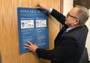 Letcher Circuit Court Clerk Mike Watts taped a poster touting the new driver's licenses to a door in his office on Tuesday. (Eagle photo)