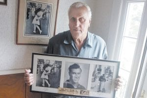 George Mendonsa posed for this 2009 photo in Middletown, R.I., holding a copy of the famous Alfred Eisenstadt photo of Mendonsa kissing a woman in a nurse's uniform in Times Square on Aug. 14, 1945, at the end of World War II. Mendonsa died Sunday, he was 95. It was years after the photo was taken that Mendonsa and Greta Zimmer Friedman, a dental assistant in a nurse's uniform, were confirmed to be the couple. (Providence Journal via AP)