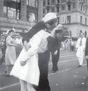 In this Aug. 14, 1945 file photo provided by the U.S. Navy, a sailor and a woman kiss in New York's Times Square, as people celebrate the end of World War II. The ecstatic sailor shown kissing a woman in Times Square celebrating the end of World War II has died. George Mendonsa was 95. This image was taken by U.S. Navy photographer Victor Jorgensen. The photo is of the same moment that photographer Alfred Eisenstaedt captured and first published in Life magazine. (Victor Jorgensen/U.S. Navy, File)