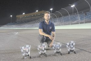 Ray Alfalla with his awards on the track at Homestead-Miami Speedway in Homestead, Fla. Alfalla is in the elite class of drivers who have mastered virtual iRacing, an online simulation of the real deal each week in NASCAR. (Bryan Blackford/Snowcone Productions via AP)