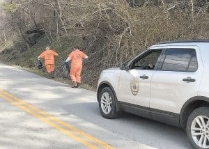 Letcher County Jail inmates Margaret Harris and Rose Newsome were protected from traffic by an SUV driven by Deputy Jailer Elena Hensley while the two were picking up trash last week at Eolia. Harris and Newsome are the first two permitted to take part in a female work-release program. (Eagle Photo)