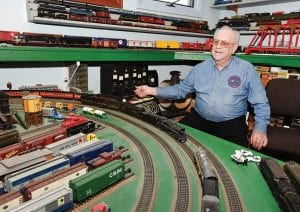 Eddie James runs some of his model railroad trains inside his home in Owensboro, Ky. Authentic antique railway lanterns hang from the kitchen ceiling beside small wind chimes cut in locomotive shapes. (Alan Warren/ The Messenger- Inquirer via AP)
