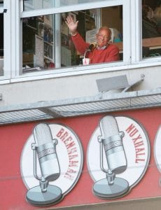 Cincinnati Reds broadcaster Marty Brennaman waves to the crowd during a baseball game against the Los Angeles Angels in Cincinnati in April 2013. Brennaman is retiring after the 2019 season. (AP Photo)
