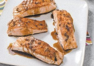 This photo provided by America's Test Kitchen shows Sweet And Tangy Glazed Salmon.