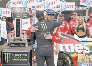 Kyle Busch, facing camera, gets a hug from brother Kurt Busch after winning the NASCAR Cup Series auto race at Bristol Motor Speedway in Bristol, Tenn. (AP Photo)