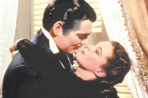 """This image released by Turner Classic Movies shows Clark Gable, left, and Vivien Leigh in a scene from """"Gone with the Wind,"""" the film that TCM first transmitted in April 1994. (Turner Classic Movies via AP)"""