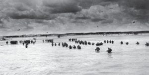 In this June 1944 photo, U.S. reinforcements wade through the surf as they land at Normandy in the days following the Allies' D-Day invasion of occupied France. June 6, 2019, marks the 75th anniversary of D-Day, the assault that began the liberation of France and Europe from German occupation. (U.S. Coast Guard via AP)
