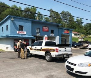 Officers with the Letcher County Sheriff 's Department looked at evidence early Monday night after the arrest of Green Russell Davis, 59, on drug and weapons charges. The arrest took place in front of the Parts City auto parts and repair shop in downtown Isom. (Photo courtesy James Hubbard)