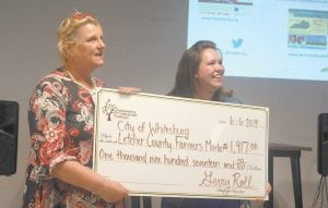Valerie Horn (left) accepts a check for the City of Whitesburg Letcher County Farmers Market from Kristin Collins, associate executive director of The Foundation for Appalachian Kentucky. Collins presented the check at a community health forum organized by The Foundation for a Healthy Kentucky in Whitesburg. (Photo by Sam Adams)