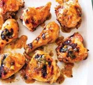 "This photo provided by America's Test Kitchen shows Peach-Glazed Grilled Chicken. This recipe appears in the cookbook ""Master of the Grill."""