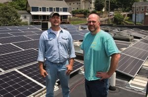 HERE COMES THE SUN -- Tony Brown and HOMES Inc. Director Seth Long stand on the roof of the HOMES Inc. building among solar collectors Long says will reduce the nonprofit corporation's power bill by two-thirds.