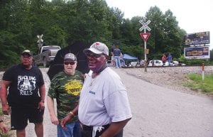 SHOW OF SUPPORT — George Massey, from left, Stanley Sturgill and Bennie Massy look on as a car horn is sounded in support of Blackjewel miners blocking a rail crossing at Cumberland. The three were among the retired UMWA miners who turned out to support Blackjewel miners on Tuesday. (Photo by Sam Adams)