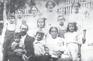 At top, James and Sarah Back Adams pose for a family photo with 11 of their 12 children outside their hillside home on Rockhouse Creek.