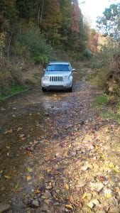 TO KINGDOM COME has long meant going to a faraway, inaccessible place, but the road at Kingdom Come Creek gives the phrase real meaning. Above, a Jeep crawls along the road, which is mostly a sand and gravel creek bed. Former Letcher County Judge/Executive Carroll Smith said the road splits his property and crosses the creek nine times. It is inaccessible to emergency vehicles and any vehicle that isn't four-wheel drive, Smith told the Letcher County Fiscal Court on Monday. He is asking the court to do something about the road so his property can be protected. (Photo by Sam Adams)