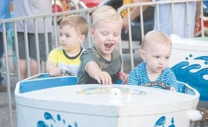 Kingston Slone, center, is thrilled with the carnival's boat ride he took with pals Carson Slone, left, and Kashden Slone, right.