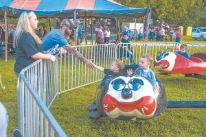 Bentley Stewart, 2, slaps five to his dad, Josh Stewart, from a ride at the Isom Days carnival. Bentley rode with his brother, Josh, and the boys' mom, Heather Stewart, watched.