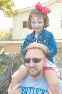 Bristol McCall enjoys her seat for the Isom Days parade on Saturday as she sits perched on the shoulders of her dad, Letcher County Magistrate Bennie McCall.