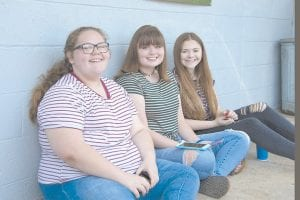 Hannah Amon, Olivia Kincer and Marie Collins beat the heat Saturday morning by watching the Isom Days Parade in the shade.