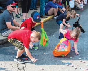 Ethan Wright (bottom left) joins Noah, Makayla and Chastity Vernon in collecting candy thrown during the Neon Days parade on Saturday.