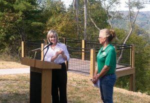 Regina Stivers, Deputy Secretary of the Kentucky Tourism, Arts and Heritage Cabinet, awarded a challenge coin to Letcher County Tourism Commission Chairwoman Missy Matthews during a ceremony on Friday naming a new overlook for Stivers's brother, the late Trooper Bennett David Combs. (All photos this page by Sam Adams)