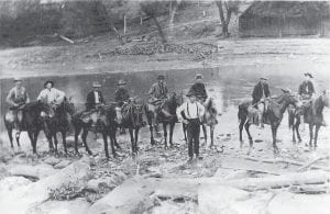These nine Letcher County men were summoned — perhaps by the Letcher County Sheriff 's Office — sometime in the early 1900's to form a posse in Whitesburg. Most probably, the posse was was given the task of conducting raids on illegal distillers of moonshine whiskey. Pictured, with most of them holding a rifle, were (from left) F.M. Blair, Boaz Adkins, D.J. Cox, Logan Morgan, Charlie Hogg, Sam Collins (standing), Cott Polly, E.L. Baker, and Butler Mullins. This photograph was taken at a ford in the North Fork of the Kentucky River in Whitesburg, near where the old Alene Theatre building (now known as Riverside Apartments) is located.
