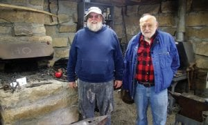 FORGING AHEAD – Bill Caudill (left), of Blackey, and Ron Stewart, of Glomawr, stand inside the blacksmith shop at the Leatherwood Memorial Park. The two are members of the Southeast Kentucky Blacksmiths Association, which built the shop from old cut stones gathered across Perry, Letcher and Knott counties. Caudill and Stewart spent Friday giving a living history lesson to students from schools across the region.